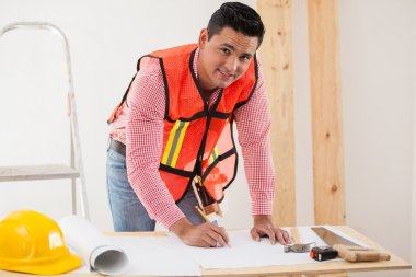 Handsome young contractor working on a remodeling design for a houseg a house