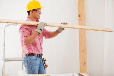 Young man wearing protective gear and carrying some wood for a constructionhouse