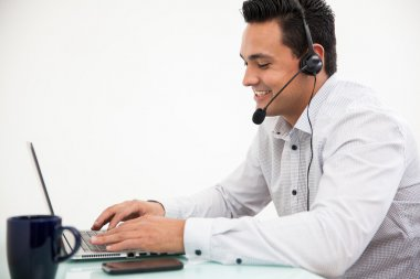 Customer service representative taking a call from a customer and smilinger