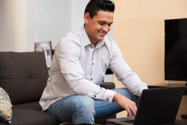 Portrait of a good-looking young man using a laptop computer to work from home home