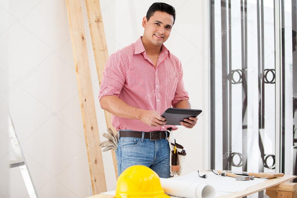 Handsome young contractor using a tablet computer at work