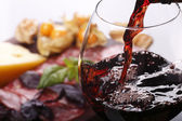Fotografie Pouring wine into glass and food background