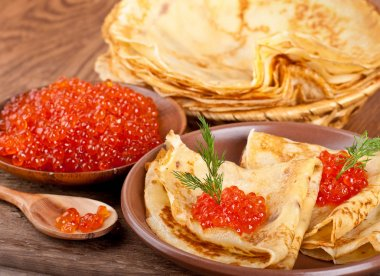Pancakes with red caviar on wooden ware