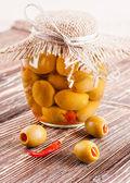 banka oliv s papričkou na dřevěném prkénku