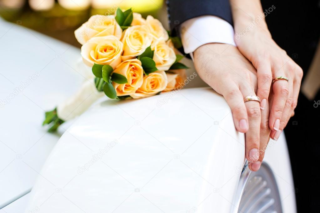 Hands of bride and groom with rings and bouquet of flowers