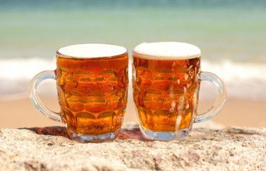 Two glasses of cold beer on the sea beach