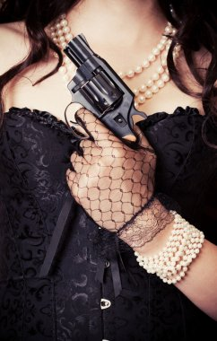 Woman wearing black corset and pearls and holding a gun against retro background stock vector