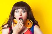 Fotografie emocionální žena nosí náušnice vyrobené z oranžové