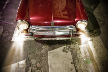 Red vintage car on road with working headlights.