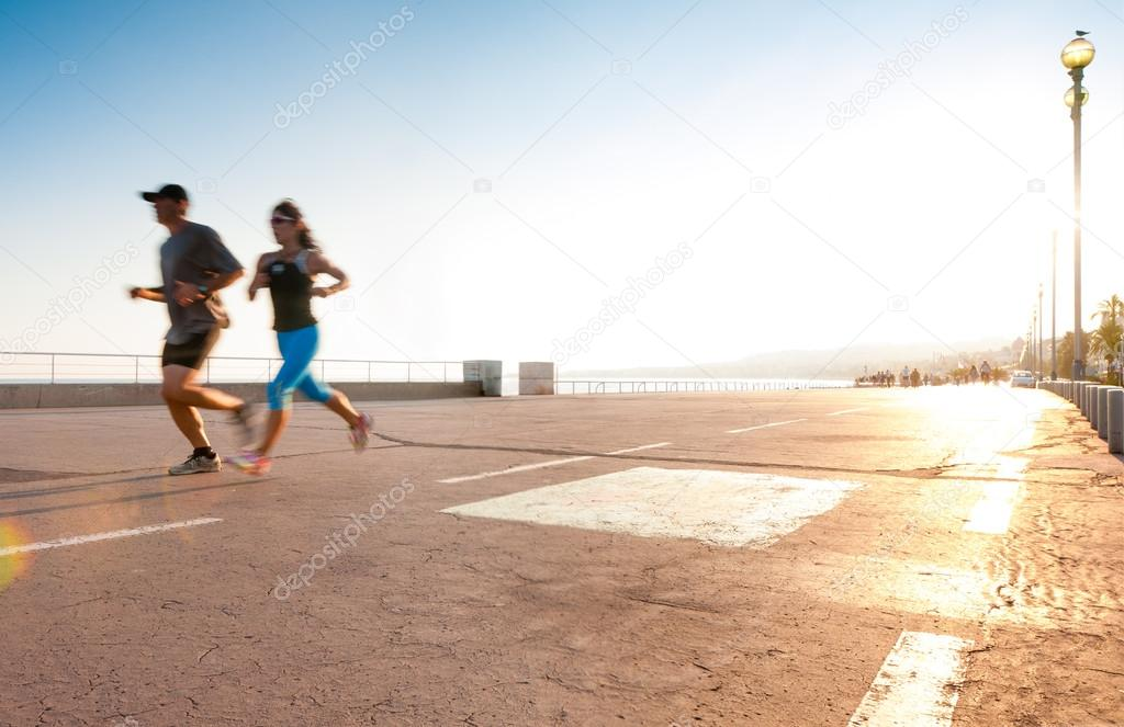 Man and woman running at the seaside.