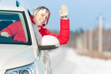 Happy beautiful woman travels by car in winter.