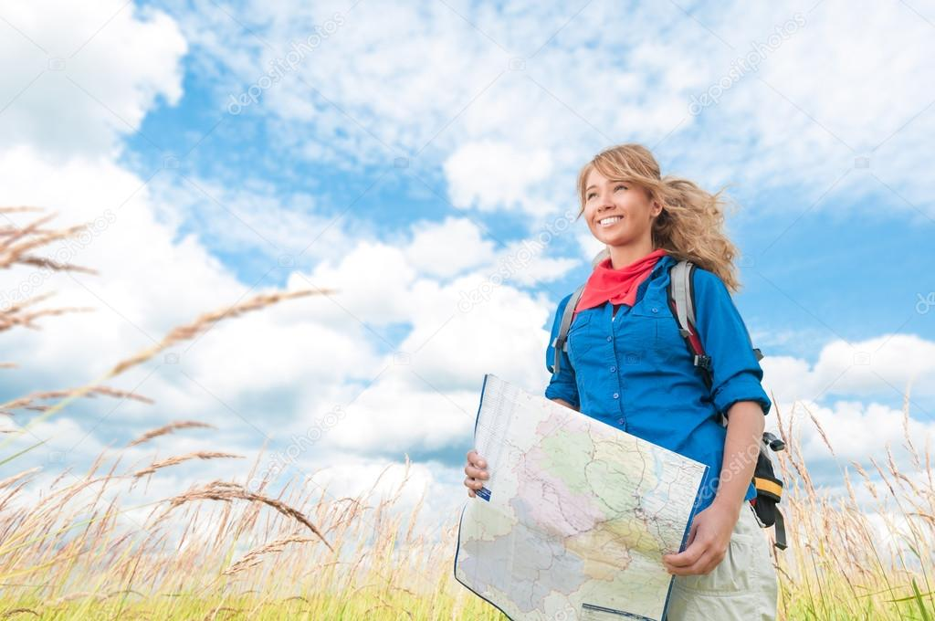 Young happy tourist woman with map in summer field.
