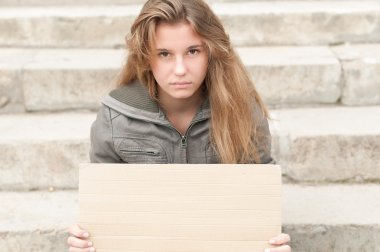 Young sad girl outdoor with blank cardboard sign.