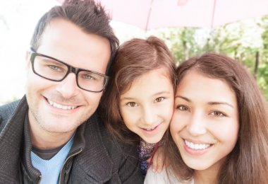Close up portrait of happy family of three.