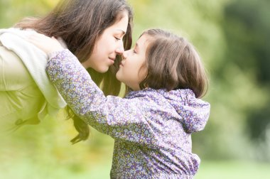 Mother and daughter looking at each other in park.
