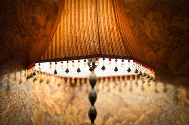 Classic lamp with dim light near wall.
