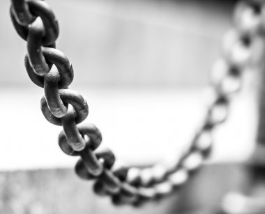 Focus on hanging metallic chain, part of fence.