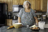 Grandma in a kitchen preparing to bake