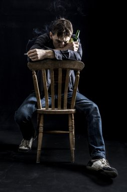 Depressed man on chair smoking cigarette with beer
