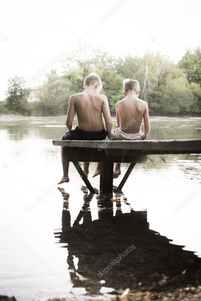 Two boy playing at the lake
