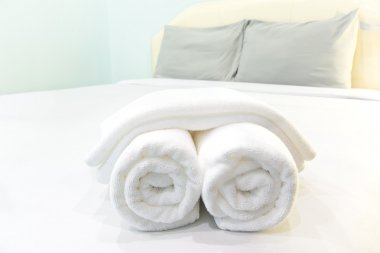 bath towels rolled on bed