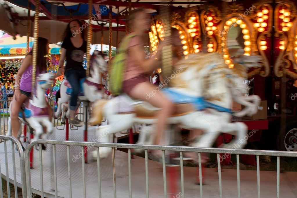 Motion Blur Of Teenagers Riding Carousel At Fair
