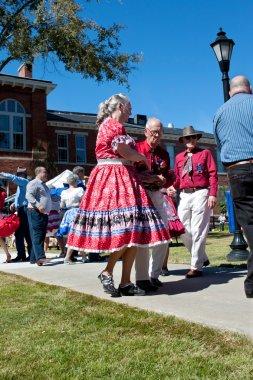 Senior Citizen Couple Square Dances At Outdoor Event