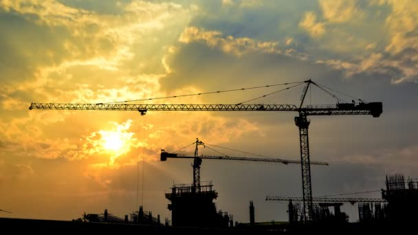 Time lapse silhouette crane working in construction site on sunset time