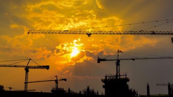 čas zániku Západu a silueta jeřáb pracuje ve velké staveniště (oddálení)