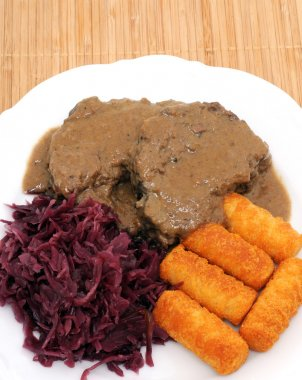 Roast of wild boar with red cabbage and potato croquettes