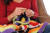 eine midaged Frau mit bayerischen Dirndl mit bunten Wolle stricken