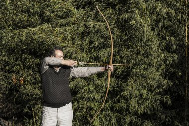 Archer with Antique Bow and Arrow Aiming