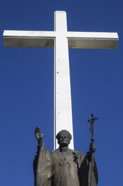 White Cross behind Statue of Pope John Paul II