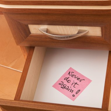 Paper reminder in open desk drawer
