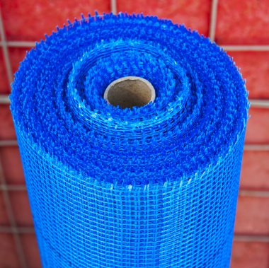 roll of plastic mesh on red background