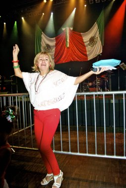 Woman from Mexico dances with a plate of food
