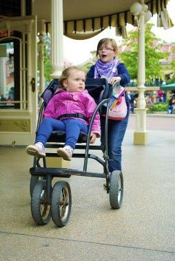 Girl carries her sister in a pram