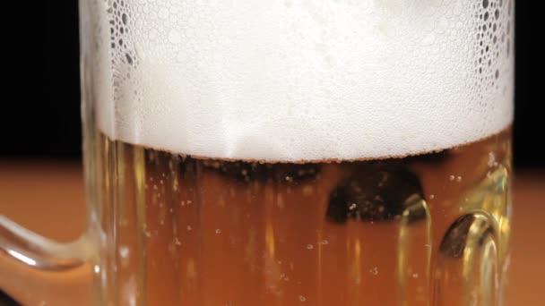 nalil pivo ve skle na černém pozadí