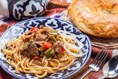 Uzbek national food on traditional fabric adras