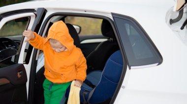 Little boy climbing out of a car