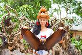 Frau im Kopfschmuck hält eine Flying-fox