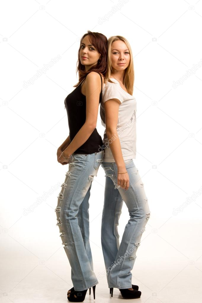 Two trendy young women standing back to back