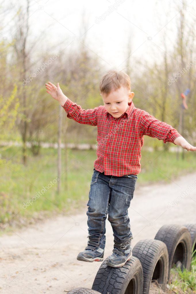Small boy balancing on old tyres