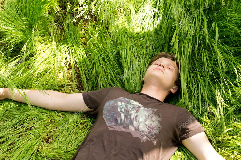 Young man sleeping in long green grass