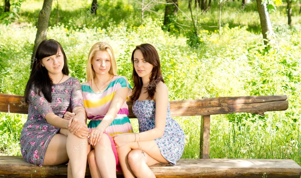 Three attractive girls on a wooden bench