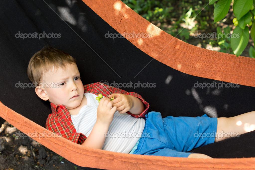 A cute kid lying on the swing