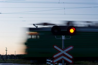 Speeding train passing a level crossing