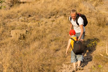 Little boy with a backpack climbing a mountain