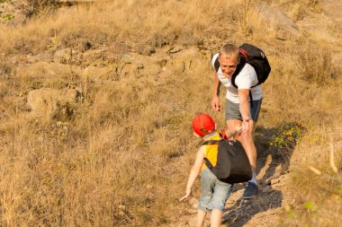 Young boy climbing a mountain with his father
