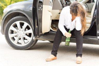 Drunk woman sitting in the door of her car